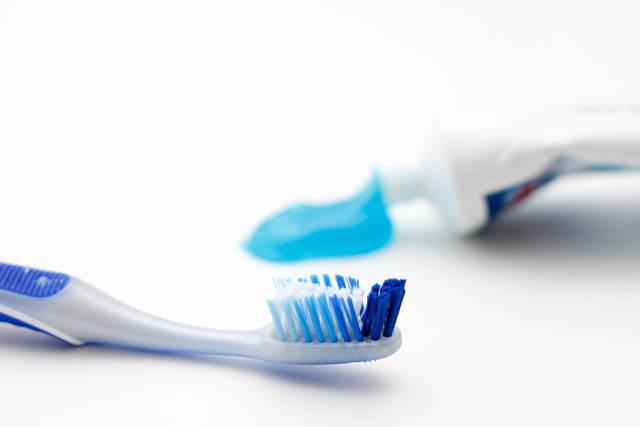 Zahnbürste mit Zahnpasta im Hintergrund