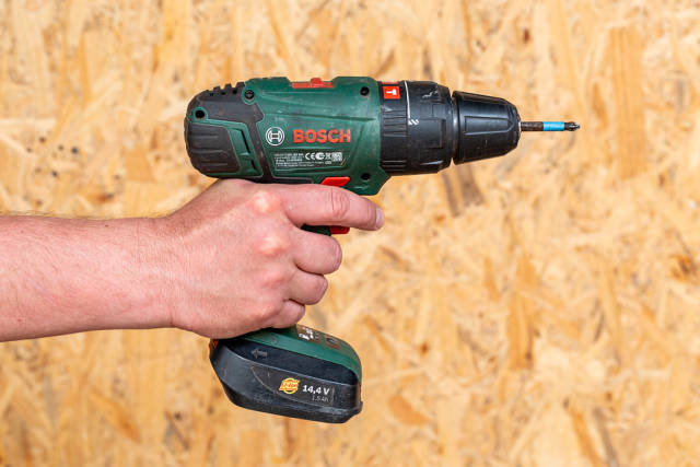 Electric drill holding a man in his hand