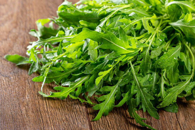 Fresh arugula on brown wooden background close-up