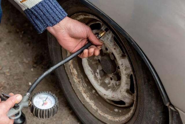 Ein Mann überprüft dein Reifendruck eines Autos mit einem Reifendruckmesser