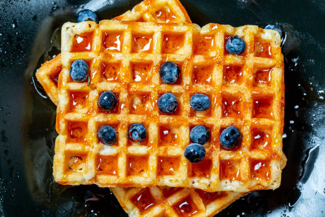 Belgian waffles poured with honey and blueberries. Top view