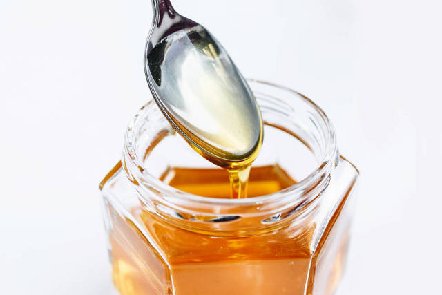 Golden Honey Pouring From The Spoon