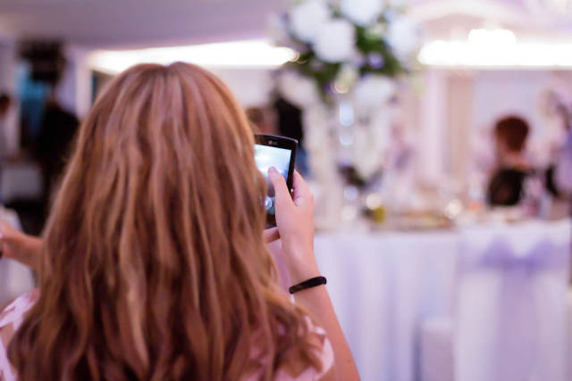 Girl taking photo with a smartphone at a wedding
