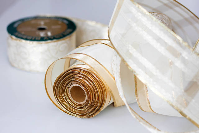 Goldfarbene Schleife für Weihnachtsgeschenke vor weißem Hintergrund