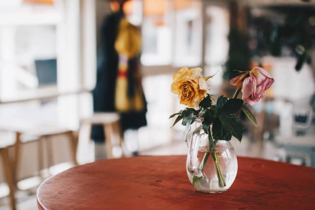 Vase mit Blumen in einem Café. Bunter, unscharfer Hintergrund