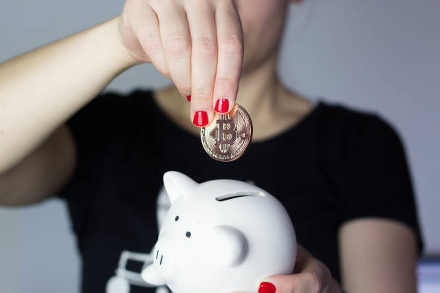 Girl saving bitcoin in piggy bank