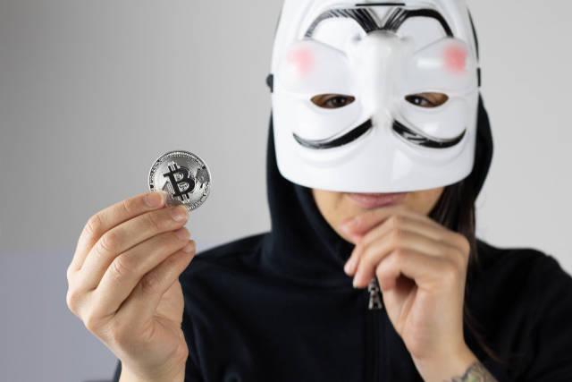 Mädchen mit weißer Maske hält eine Bitcoin Münze in der Hand