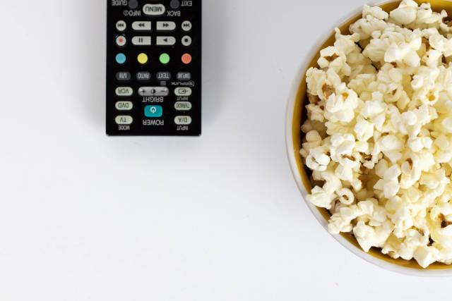 Schüssel mit Popcorn und Fernbedienung vor weißem Hintergrund