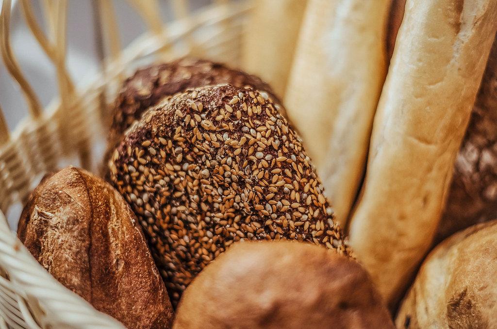 Geflochtener Korb mit frischem Brot verschiedener Sorten