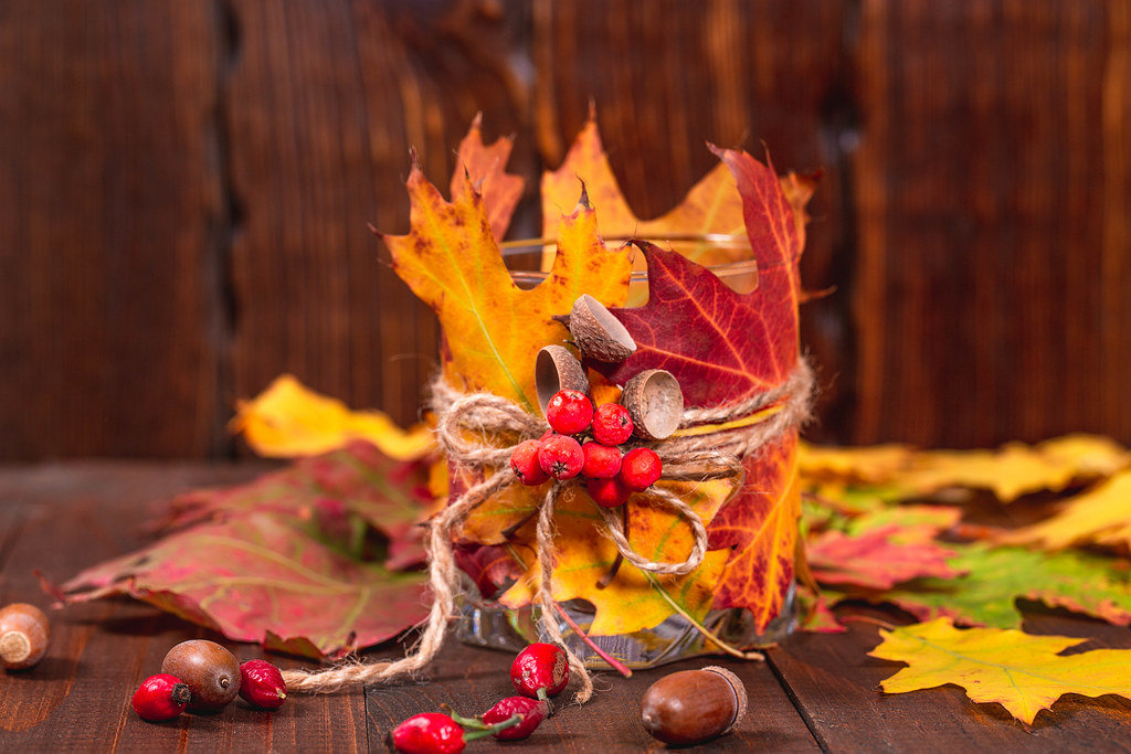 Candlestick with autumn leaves and Rowan berries on a wooden background with acorns and rose hips