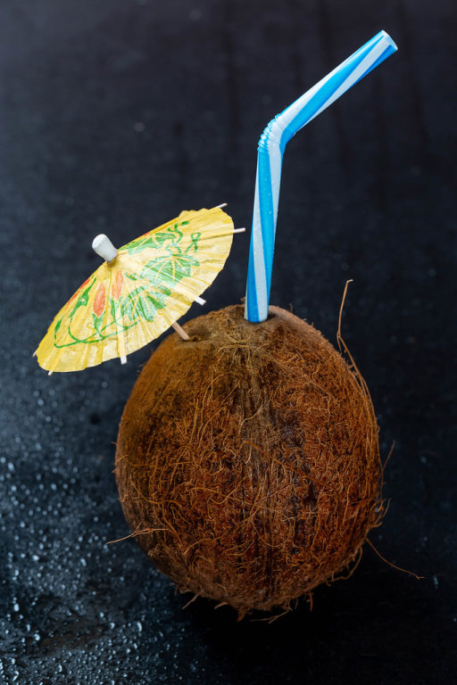 Coconut cocktail with an umbrella and a straw