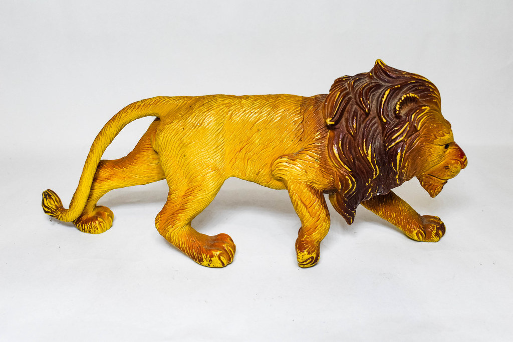 Plastic male lion toy on white surface