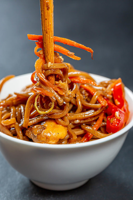 Buckwheat noodles (soba) in a white bowl with sauce, vegetables and chopsticks on black background