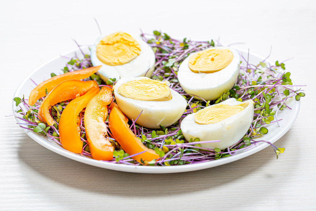 Micro-greens cabbage with boiled eggs and pieces of bell pepper