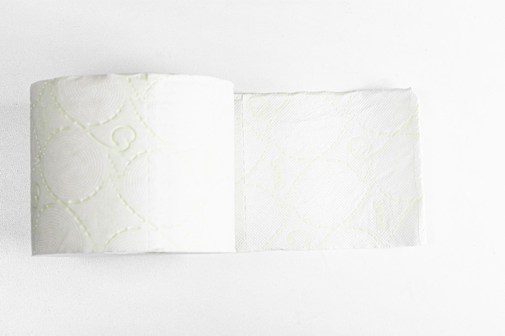 Roll of soft white toilet paper on a white background, top view