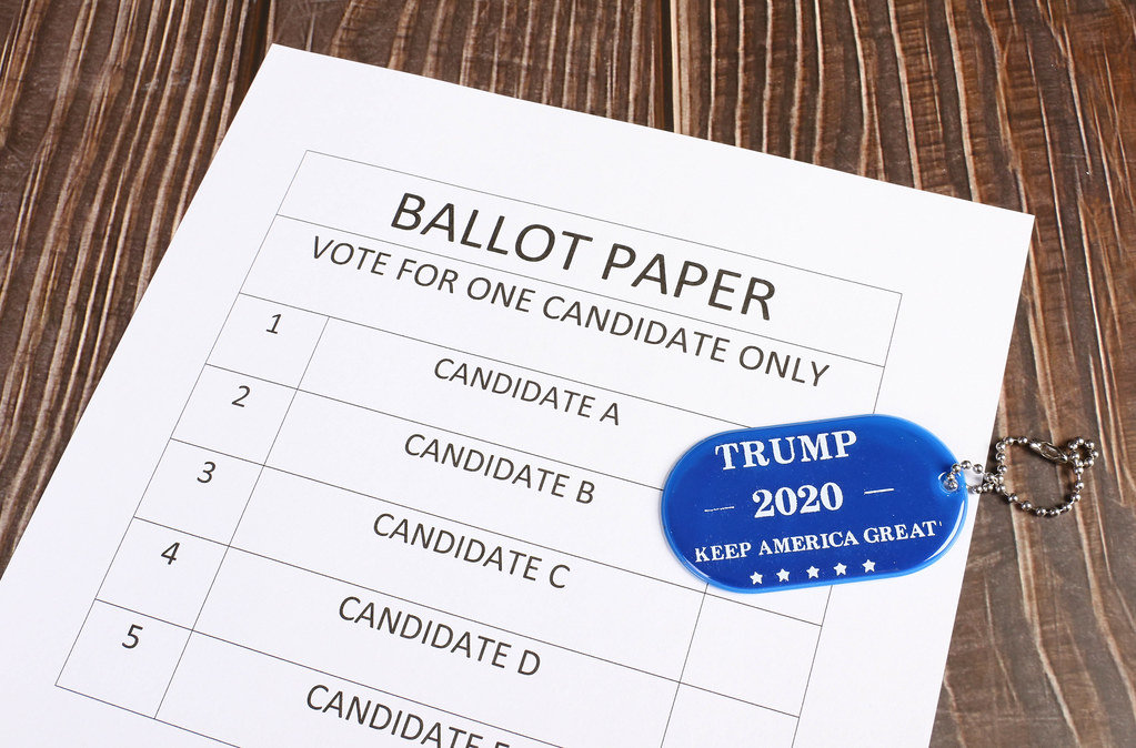 Ballot paper with blue military tag with Trump 2020 text on wooden table
