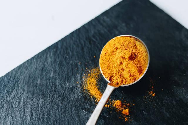 Curcuma powder in a spoon. Close up
