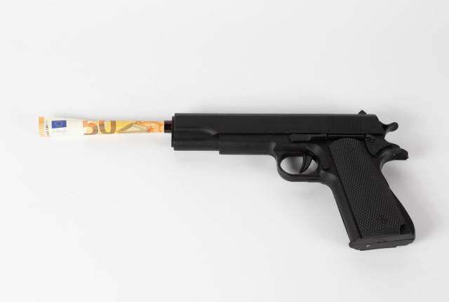 Geldschein ragt aus dem Lauf einer Pistole heraus. Gewalt ist profitabel