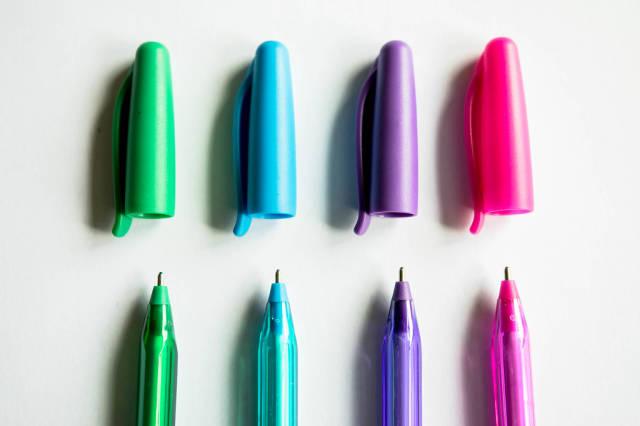 Eine Reihe bunter Kugelschreiber mit abgenommenen Kappen