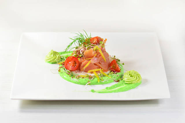 Salmon with radish sprouts, tomatoes and avocado paste