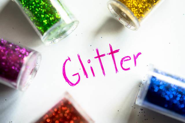 Das Wort GLITTER mit Glitzer-Fläschchen drumherum