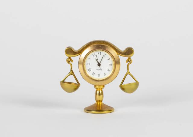 Goldene Waage mit Uhr