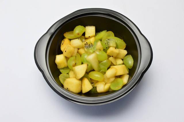 Fruchtsalat mit Birnen, Weintrauben und Kiwi in schwarzer Schüssel