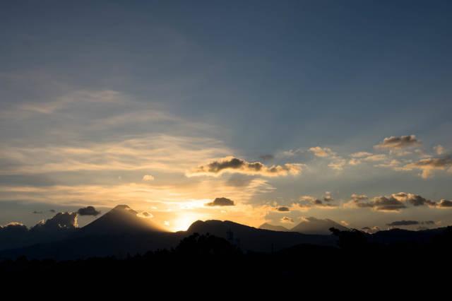 Dramatischer Sonnenuntergang hinter Vulkanbergen
