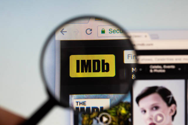 IMDb logo on a computer screen with a magnifying glass