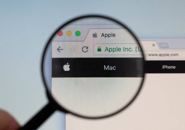 Apple logo on a computer screen with a magnifying glass