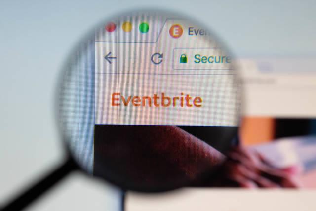 Eventbrite-Logo am PC-Monitor, durch eine Lupe fotografiert
