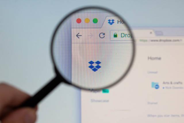 Dropbox-Logo am PC-Monitor, durch eine Lupe fotografiert