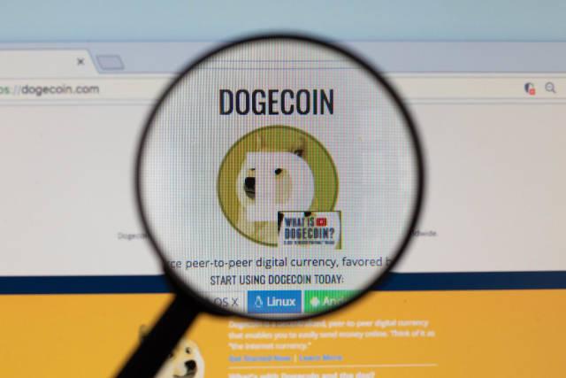 Dogecoin-Logo am PC-Monitor, durch eine Lupe fotografiert