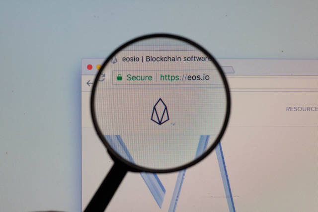 EOS-Logo am PC-Monitor, durch eine Lupe fotografiert
