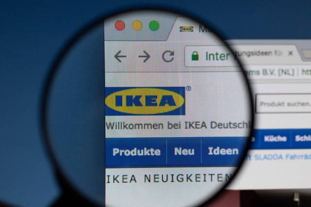 Ikea-Logo am PC-Monitor, durch eine Lupe fotografiert