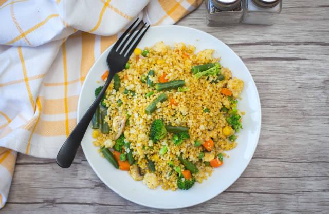 Draufsicht von Kuskus mit Brechbohnen, Brokkoli, Karotten und Erbsen