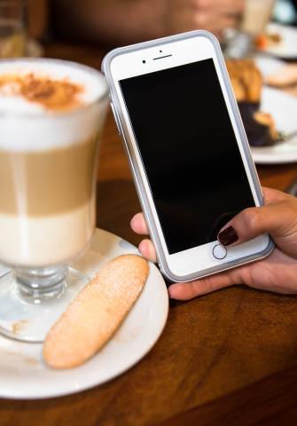 Hand hält ein Handy in einem Café