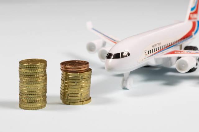 Münzstapel vor einem Flugzeug