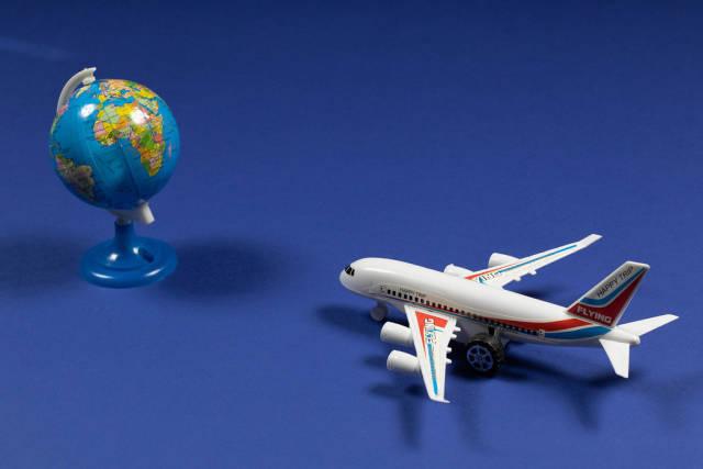 Zeit für eine Reise. Symbolbild mit Miniaturflugzeug und Globus