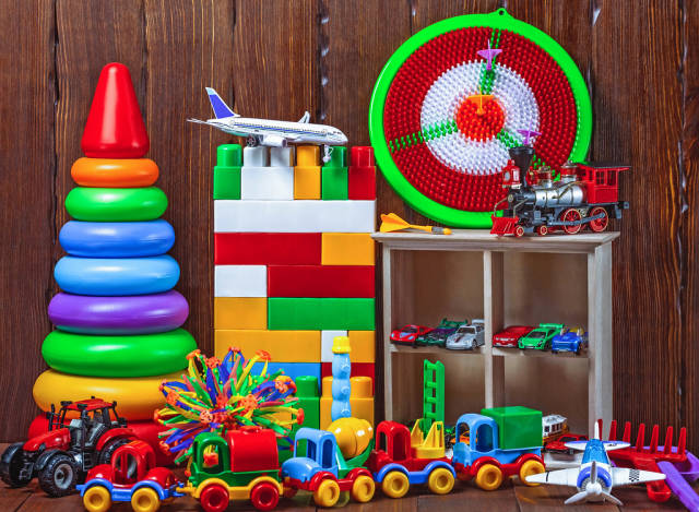 Childrens values: toys, pyramid, darts, cars, train on a wooden background