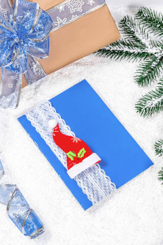 Merry Christmas card and gift box handmade on winter new year background. Preparing for the holidays