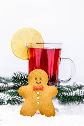 Christmas background with mulled wine and snow-covered Christmas tree branches and gingerbread man