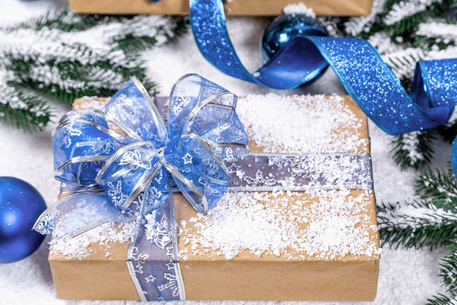 Gift box with blue ribbon and bow, toys and decor on new year background