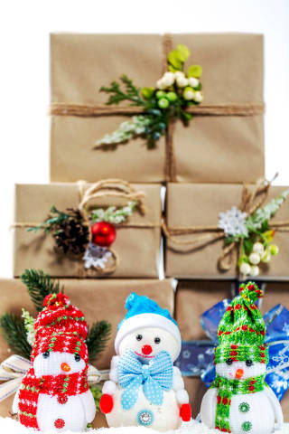 Christmas background with gifts and snowmen on snow