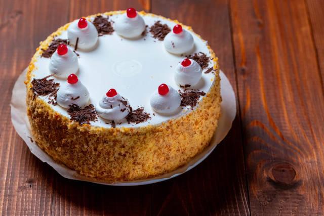 Beautiful birthday cake on wooden background