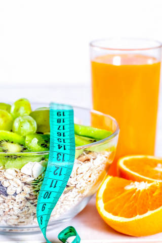 Glass of fresh juice, oatmeal with kiwi and oranges for Breakfast for weight loss with measuring tape