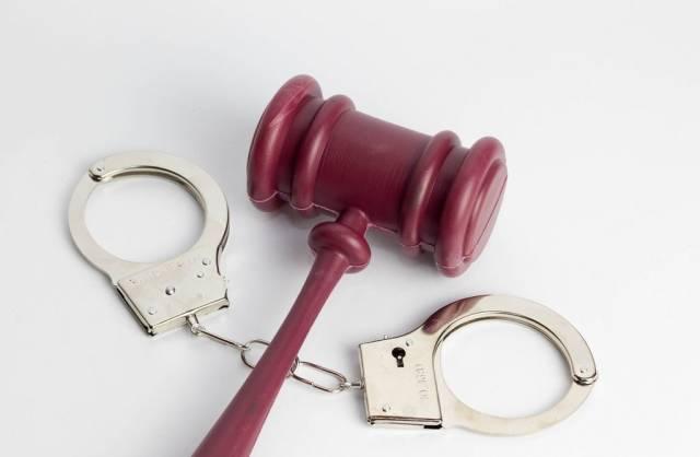 Ein Richterhammer mit Handschellen auf weißem Hintergrund