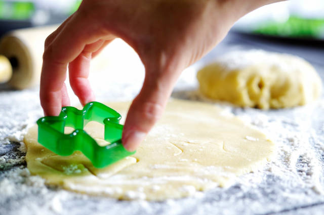 Hand lifting angel cookie cutter from dough
