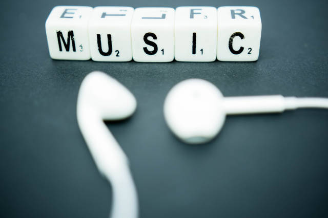 Letter dice reading MUSIC with earphones