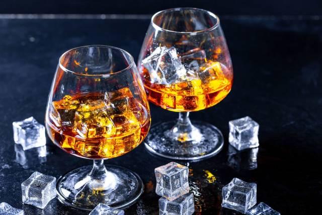 Zwei Cognacgläser mit Eiswürfeln auf dunklem Untergrund
